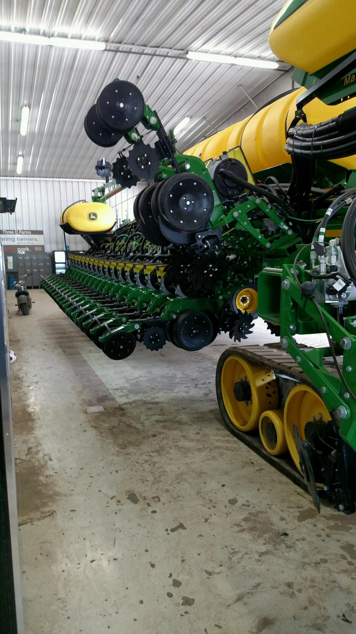 Shop photo of the row unit mount in between single wheel fertilizer opener folded up
