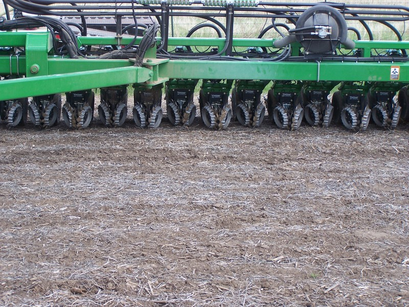 Front facing view of multiple floating row cleaners and shark tooths operating in the field
